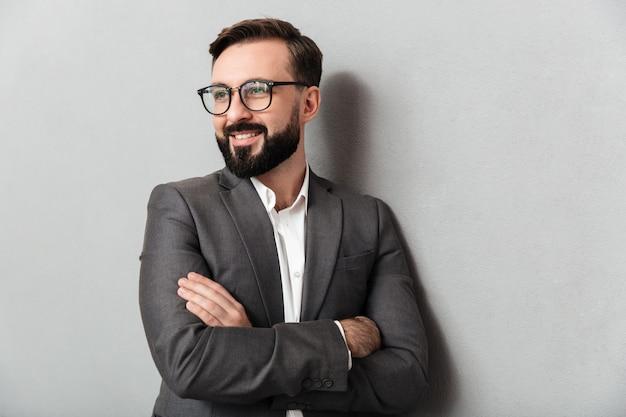 Close up ritratto di compiaciuto uomo senza barba in occhiali alla ricerca sulla fotocamera con un sorriso sincero, in piedi con le braccia conserte isolato su grigio