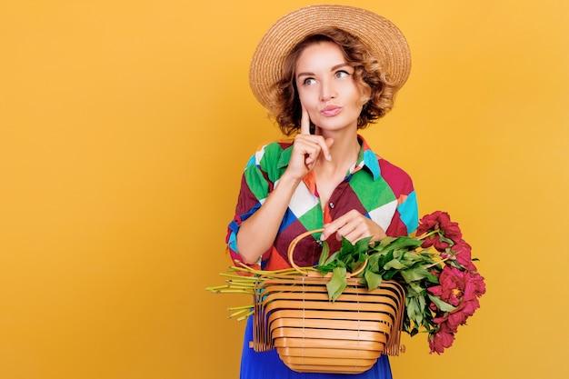 Close up ritratto di donna pensosa con acconciatura riccia con bouquet di pioni nelle mani. sfondo muro giallo.