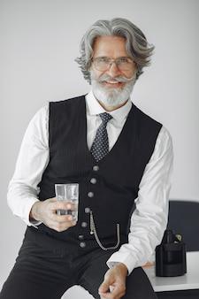 Close up ritratto di ghignare uomo vecchio stile. nonno con un bicchiere d'acqua.