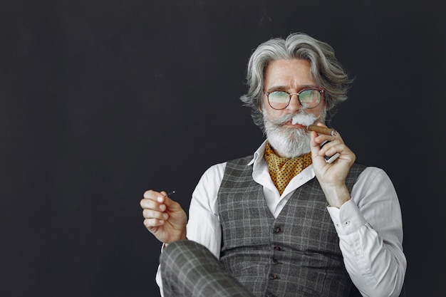Close up ritratto di ghignare uomo vecchio stile. nonno con un sigaro e whisky.
