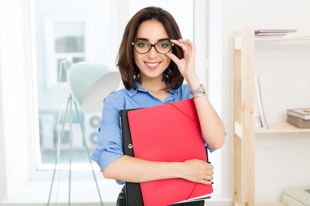 Close-up ritratto di giovane ragazza bruna in camicia blu in piedi in ufficio. ha in mano le cartelle e sorride felice alla telecamera