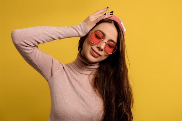 Close up ritratto di hipster giovane donna con i capelli lunghi che indossa il vetro rotondo rosa e berretto che tocca la sua testa e sorridente con gli occhi chiusi.