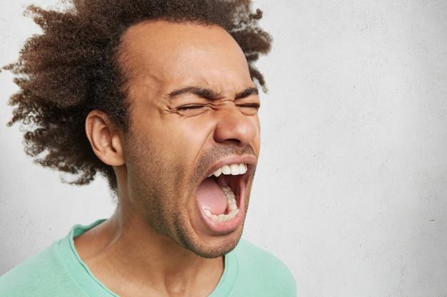 Close up ritratto di pazzo arrabbiato giovane maschio dalla pelle scura grida di rabbia e furia