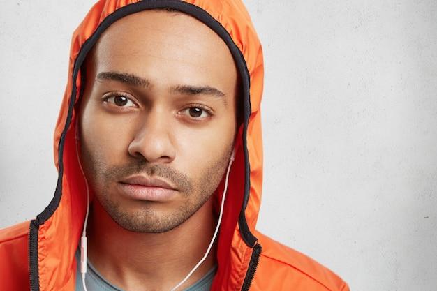 Close up ritratto di razza mista dalla pelle scura maschio con stoppie, indossa il cappuccio