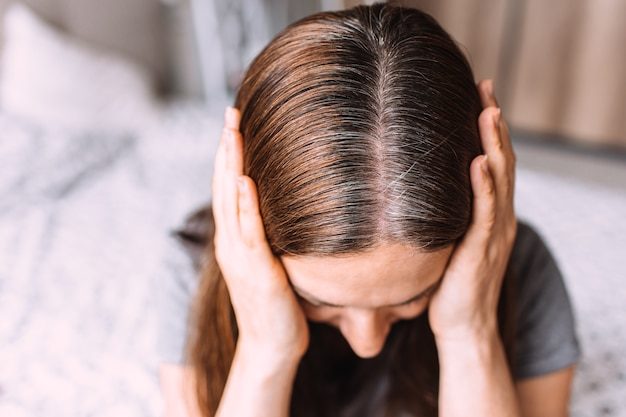 Close up ritratto di una giovane donna con ricresciuti capelli grigi radici radici.