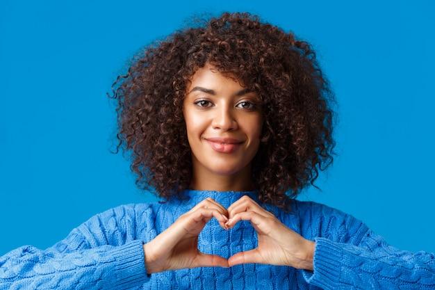 Close-up ritratto tenero e carino afro-americana romantica donna esprimere i suoi sentimenti con gesto, mostrando il segno del cuore e sorridente, avere simpatia, confessare sul blu
