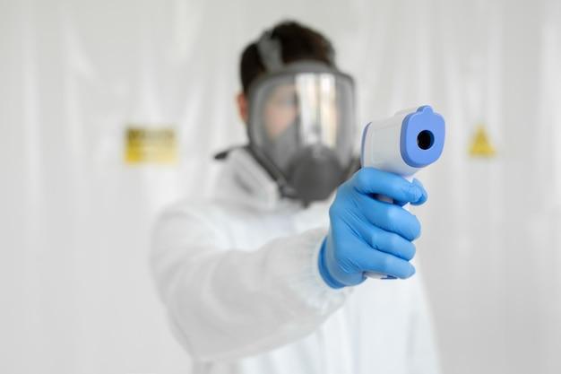 Close-up shot del medico che indossa una maschera respiratoria protettiva pronto per l'uso a infrarossi sulla fronte termometro pistola per controllare la temperatura corporea per i sintomi del virus epidemia virus epidemia concetto coronavirus