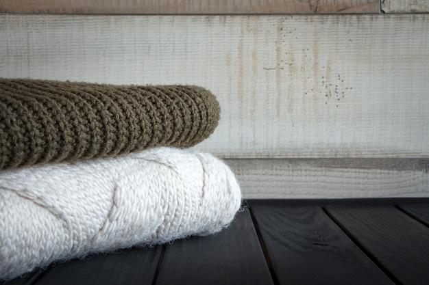 Close-up shot di due a maglia da maglioni di lana naturale, su un tavolo di legno nero,