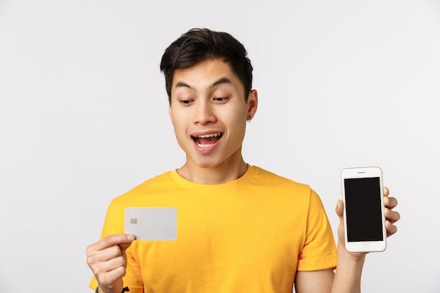 Close-up shot ragazzo entusiasta deciso mettere deposito di denaro, ottenere credito per pagare il viaggio, tenendo il telefono che mostra display e carta bancaria, sorridente divertito, in piedi muro bianco