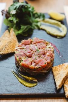 Close up tartare di tonno rosso piccante con salsa agrodolce e piccante. servito con pane tostato e insalata su lastra di pietra nera.