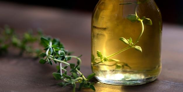 Close up timo olio essenziale in una bottiglia con basilico fresco