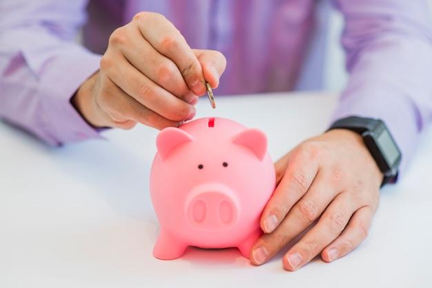 Close up vista della mano di un uomo che mette una moneta nella fessura di una banca salvadanaio in un concetto di risparmio e di investimento