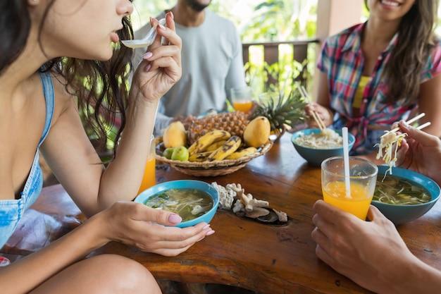 Closeup colpo di giovani mentre si mangia la zuppa di spaghetti gruppo di amici godono cibo tradizionale asiatico