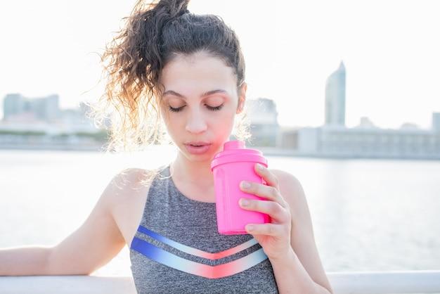 Closeup della ragazza sportiva sexy bevendo dal fiume della città