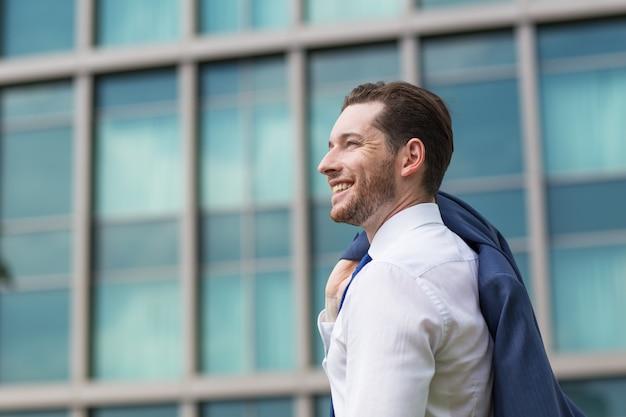 Closeup di uomo d'affari felice che si leva in piedi fuori
