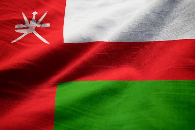 Closeup of ruffled oman flag, oman flag blowing in wind