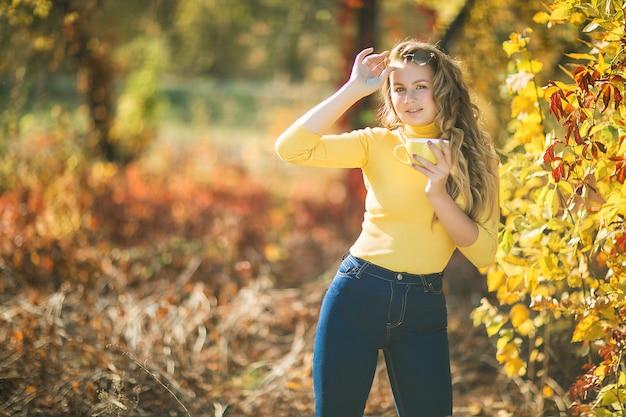 Closeup ritratto di giovane bella donna in autunno. elegante donna attraente in autunno. donna bionda con capelli ricci, bere il caffè.