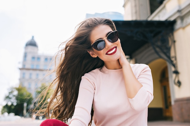 Closeup ritratto di ragazza attraente in occhiali da sole con labbra vinose in città. i suoi lunghi capelli volano nel vento, sorride con un sorriso bianco come la neve.