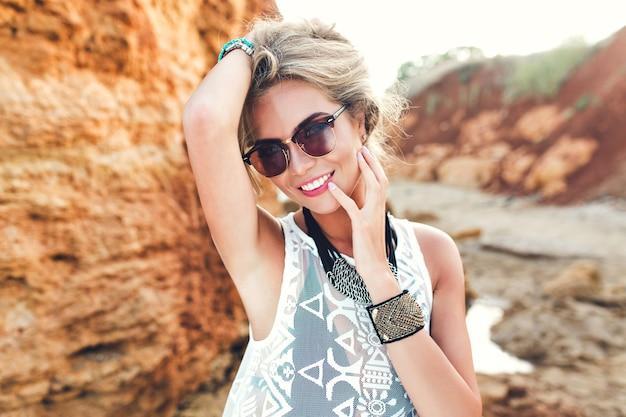 Closeup ritratto di ragazza bionda con i capelli lunghi in posa per la fotocamera su sfondo di rocce. tiene i capelli sopra e sorride alla telecamera.