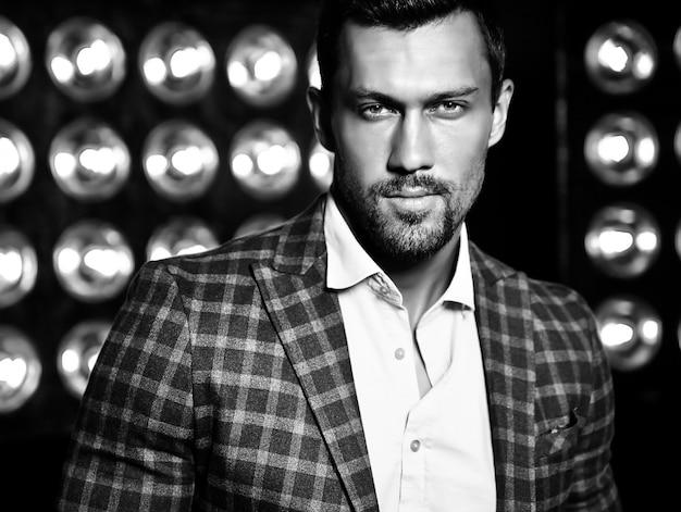 Closeup ritratto di uomo di modello maschio sexy moda bello vestito in abito elegante su sfondo nero luci studio