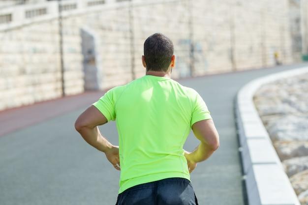 Closeup vista posteriore di uomo forte che corre sulla strada