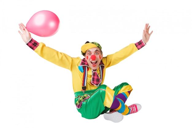 Clown siots con un palloncino in una mano isolata su uno sfondo bianco