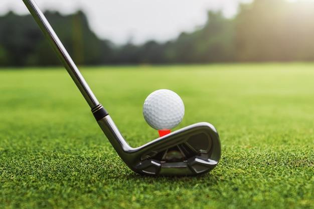 Club di golf e palla da golf del primo piano su erba verde con il tramonto