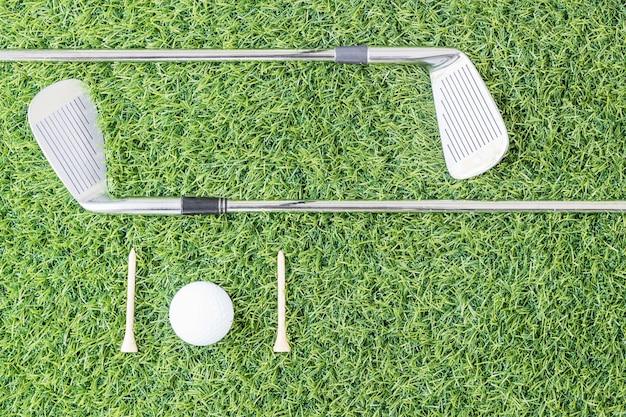 Club di golf e palla da golf su erba verde