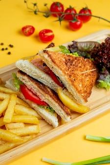 Club sandwich con contorno di erbe e patatine fritte