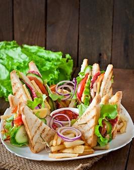 Club sandwich con formaggio, cetriolo, pomodoro, carne affumicata e salame. servito con patatine fritte.