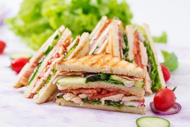 Club sandwich con petto di pollo, pancetta, pomodoro, cetriolo ed erbe