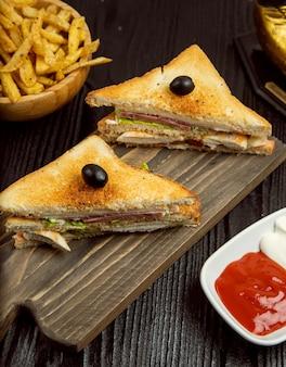Club sandwich con salame, pancetta e patatine fritte servite con ketchup, maionese in piatto di legno.