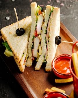 Club sandwich con salsa di peperoncino piccante e patatine fritte.
