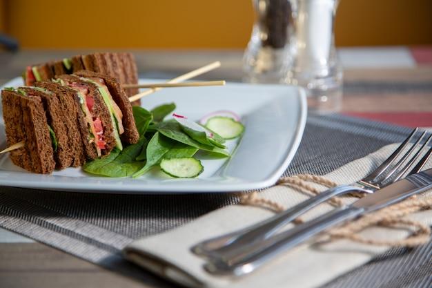 Club sandwich in un piatto bianco