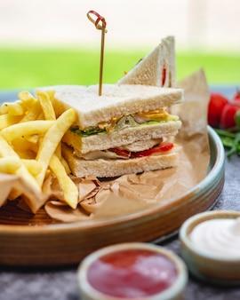 Club sandwich servito con maionese e ketchup di patatine fritte