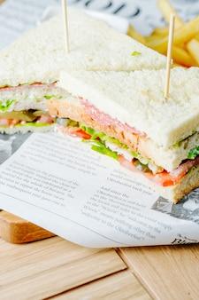 Club sandwich servito con patatine fritte
