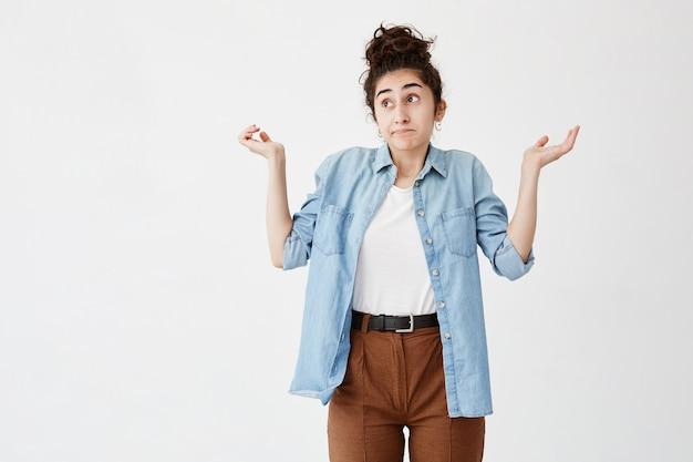 Clueless perplessa giovane donna vestita in abbigliamento casual con i capelli in panino che scrolla le spalle le spalle e fissa con sguardo confuso dopo aver fatto qualcosa di sbagliato ma non sentirsi dispiaciuta