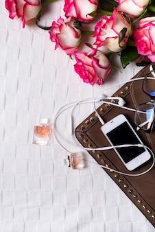 Clutch femminile con telefono, cuffie e bottiglie di profumo con fiori