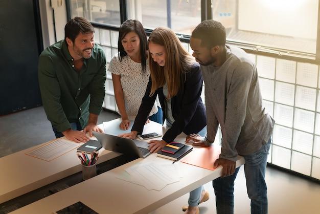 Co lavoratori in piedi su una scrivania che passa attraverso la presentazione sul computer