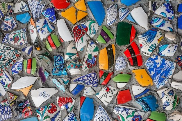 Cocci colorati di ceramica tradizionale floreale ornamentale, riutilizzati dopo la rottura per un muro all'aperto.