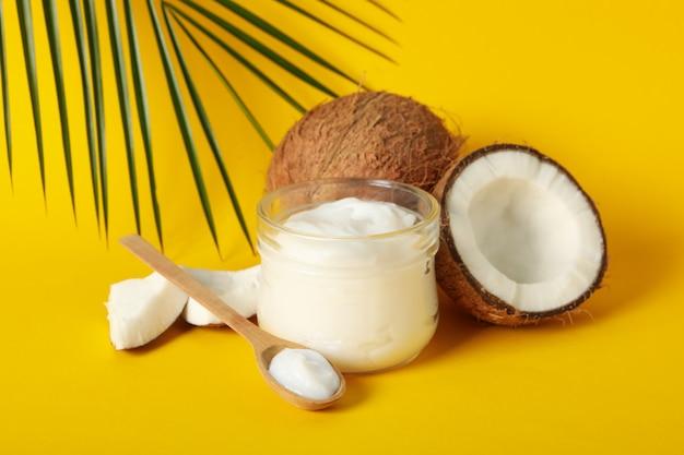 Cocco, cosmetici e ramo della palma sulla tavola gialla, fine su