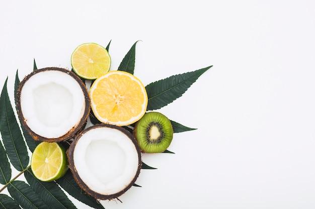 Cocco dimezzato; limone; arancia e kiwi su foglie verdi su sfondo bianco