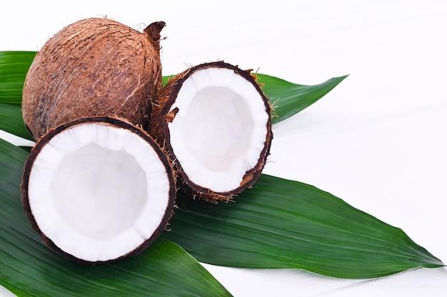 Cocco fresco in una forma rotta. frutta esotica su uno sfondo bianco. spazio libero per il testo. concetto di mangiare sano. copia spazio