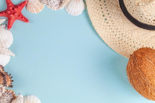 Cocco, stelle marine, conchiglie, cappello di paglia su sfondo blu