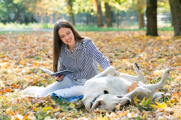 Coccole della donna adulta il suo cane nel parco