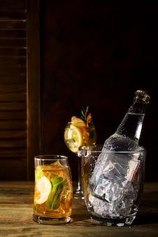 Cocktail a base di whisky con secchiello per il ghiaccio in vetro su backgorund in legno scuro