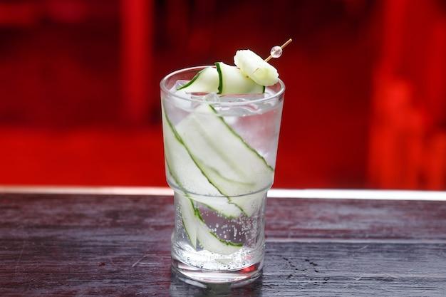 Cocktail alcolici di cetriolo e calce sulla superficie in marmo di legno. cocktail alcolici rinfrescanti di cetriolo e calce con ghiaccio su un bancone in legno.