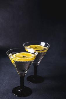 Cocktail alcolico con splash. martini secco con olive nere. cocktail termico all'interno del bicchiere da martini su sfondo scuro. i bicchieri di martini sono sul bancone.