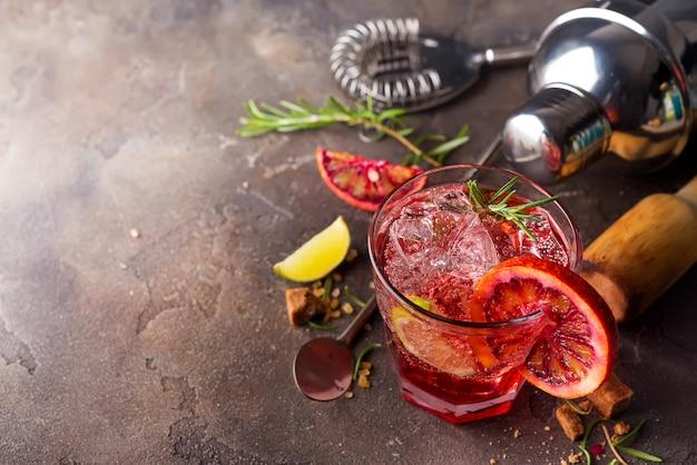 Cocktail alcolico esotico colorato fresco rosso con arancia e ghiaccio su uno sfondo di pietra.