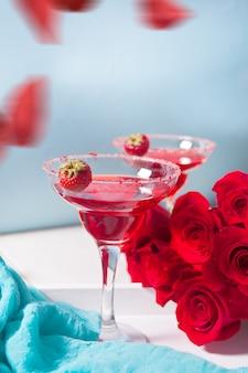 Cocktail alcolico esotico rosso in bicchieri trasparenti e petali di rose rosse sul tavolo bianco in legno per una cena romantica.